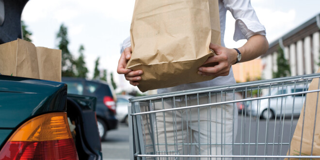 woman with bags and shopping cart loads a car